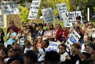 Supporters of Rep. Michele Bachmann display signs at a Tea Party at Lake George, St. Cloud, Saturday, Sept. 12, 2009. (Jason Wachter/ St. Cloud Times)