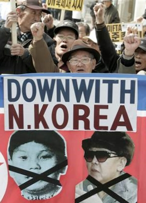 South Korean protesters with portraits of North Korean Kim Jong Il, right, and his alleged third son Kim Jong Un, shout a slogan during a rally against North Korea's recent military policy in Seoul, on March 9, 2009. (Photo: Ahn Young-joon / AP file)